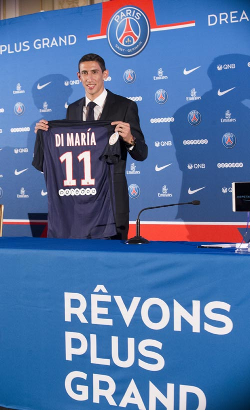 New Argentinean winger Angel Di Maria, poses with his PSG jersey during his official presentation in Paris, France. Thursday, Aug. 6, 2015.  Angel Di Maria signed a four-year deal with Paris Saint-Germain on Thursday to complete his transfer from Manchester United. (AP Photo/Jacques Brinon)