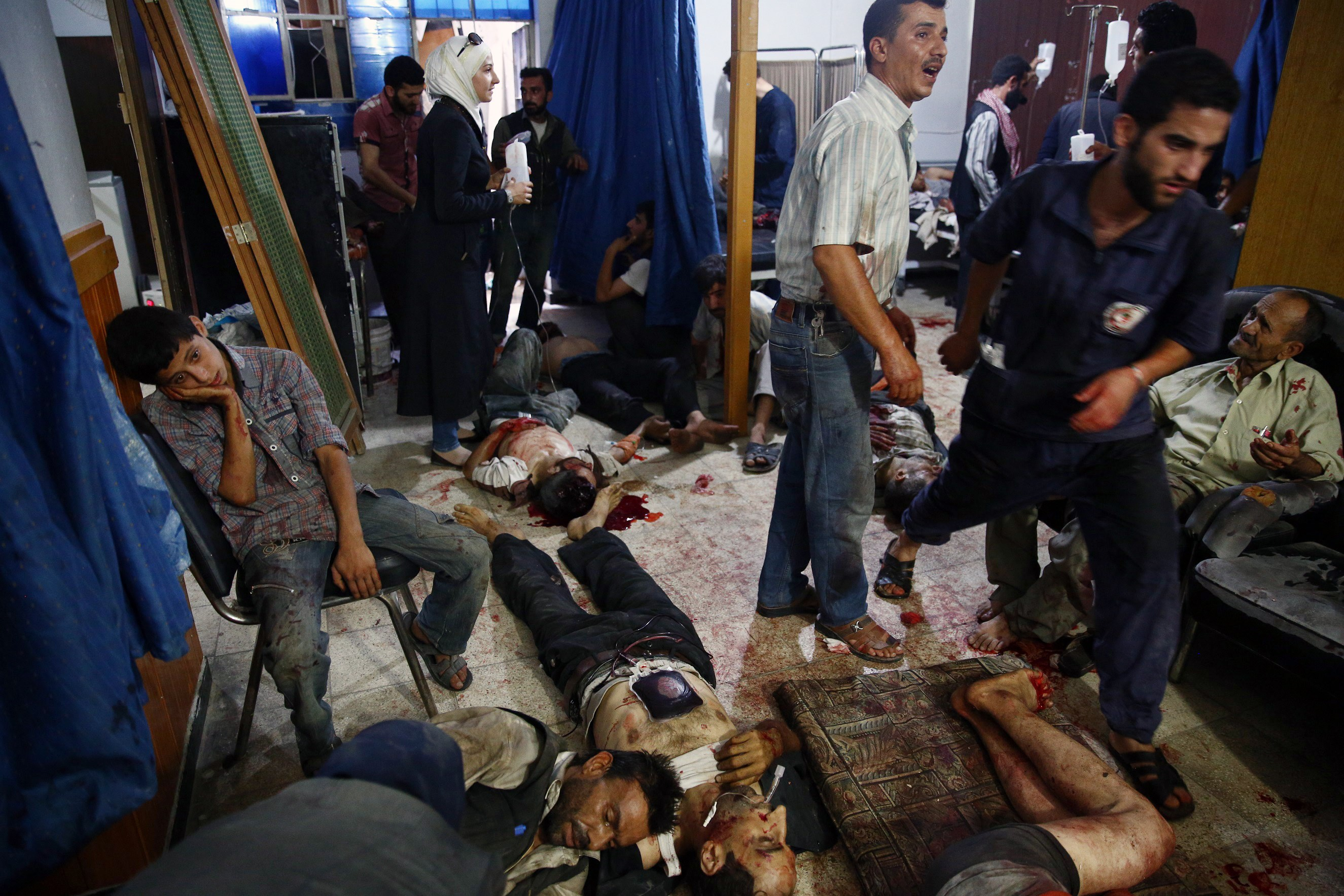 Syrian injured people receive treatment at a make-shift hospital in the rebel-held area of Douma, east of the capital Damascus, following air strikes by Syrian government forces on a marketplace on August 16, 2015. At least 70 people were killed and 200 people were injured, with the death toll -most of them civilians- likely to rise as many of the wounded were in serious condition, the Syrian Observatory for Human Rights said.    AFP PHOTO / ABD DOUMANY  SYRIA-CONFLICT