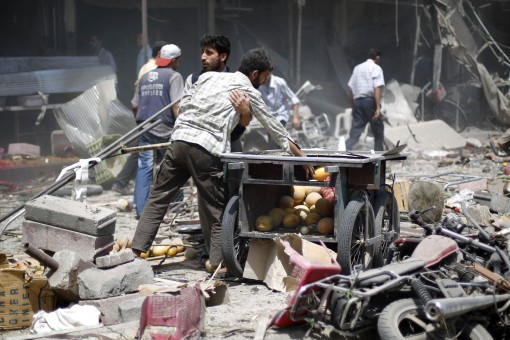 Syrian men react as they stand amid the rubble following air strikes by Syrian government forces on a marketplace in the rebel-held area of Douma, east of the capital Damascus, on August 16, 2015. At least 70 people were killed and 200 people were injured, with the death toll -most of them civilians- likely to rise as many of the wounded were in serious condition, the Syrian Observatory for Human Rights said. AFP PHOTO / SAMEER AL-DOUMY  SYRIA-CONFLICT