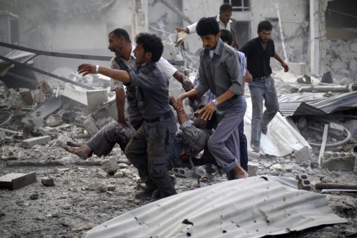 Syrian emergency personnel carry a wounded man following air strikes by Syrian government forces on a marketplace in the rebel-held area of Douma, east of the capital Damascus, on August 16, 2015. At least 70 people were killed and 200 people were injured, with the death toll -most of them civilians- likely to rise as many of the wounded were in serious condition, the Syrian Observatory for Human Rights said. AFP PHOTO / SAMEER AL-DOUMY  SYRIA-CONFLICT